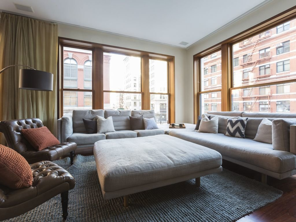 """With a large roof terrace, master bedroom with dramatic arched windows, a bedroom with curved glass walls, and a floating glass staircase, this elegant townhouse evokes the vintage cool of a """"Mad Men"""" set.  Photo 2 of 12 in Experience New York City's Eclectic Side at One of These Modern Short-Term Rentals"""