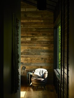 In each room, a single wall was clad in reclaimed poplar. An antique barrel chair sits in the master bedroom.   Scaly Mountain, North Carolina Dwell Magazine : September / October 2017