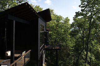One of the pitched roofs shelters a side deck, which has a SwingLab bench.   Scaly Mountain, North Carolina Dwell Magazine : September / October 2017