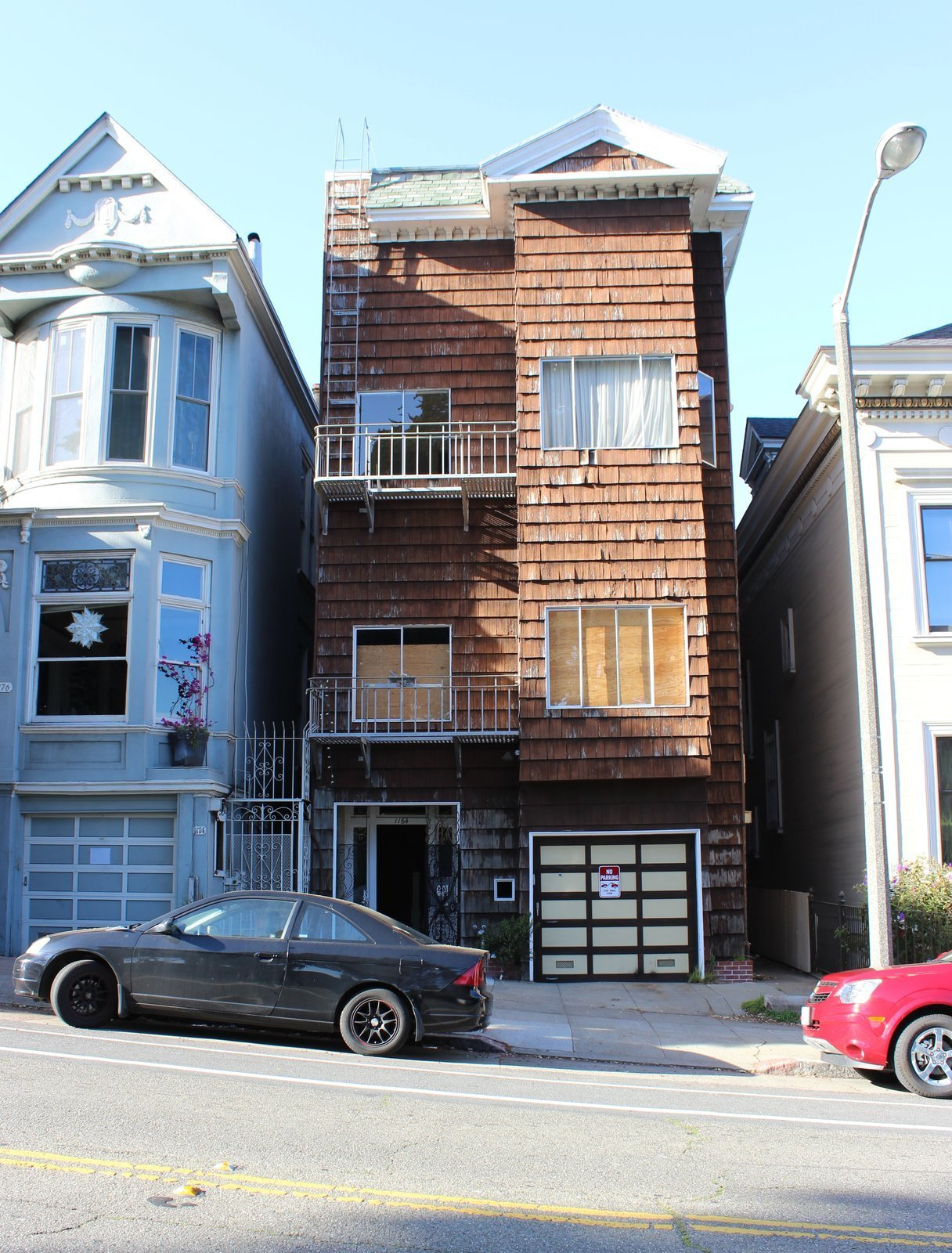 Before: Alamo Square Residence Exterior with worn and ruined brown wood shingles as siding and gable and hipped rooflines with faded green shingle roofing