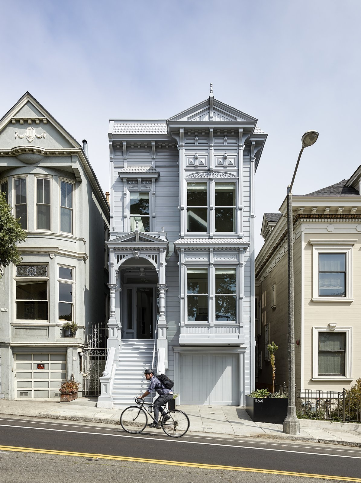 After: Alamo Square Residence Exterior with victorian style details, gable and hipped rooflines and pale metallic silver paint