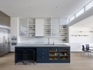 The home's kitchen features dual Miele ovens, Thermador refrigerator and freezer, and Thermador induction cooktop. A feature wall clad in natural Carrara marble sits behind sliding cabinet uppers. Paola Lenti Heron counter stools in 'verde scuro,' coordinate with custom cabinet fronts, accented with Spinneybeck leather pulls.