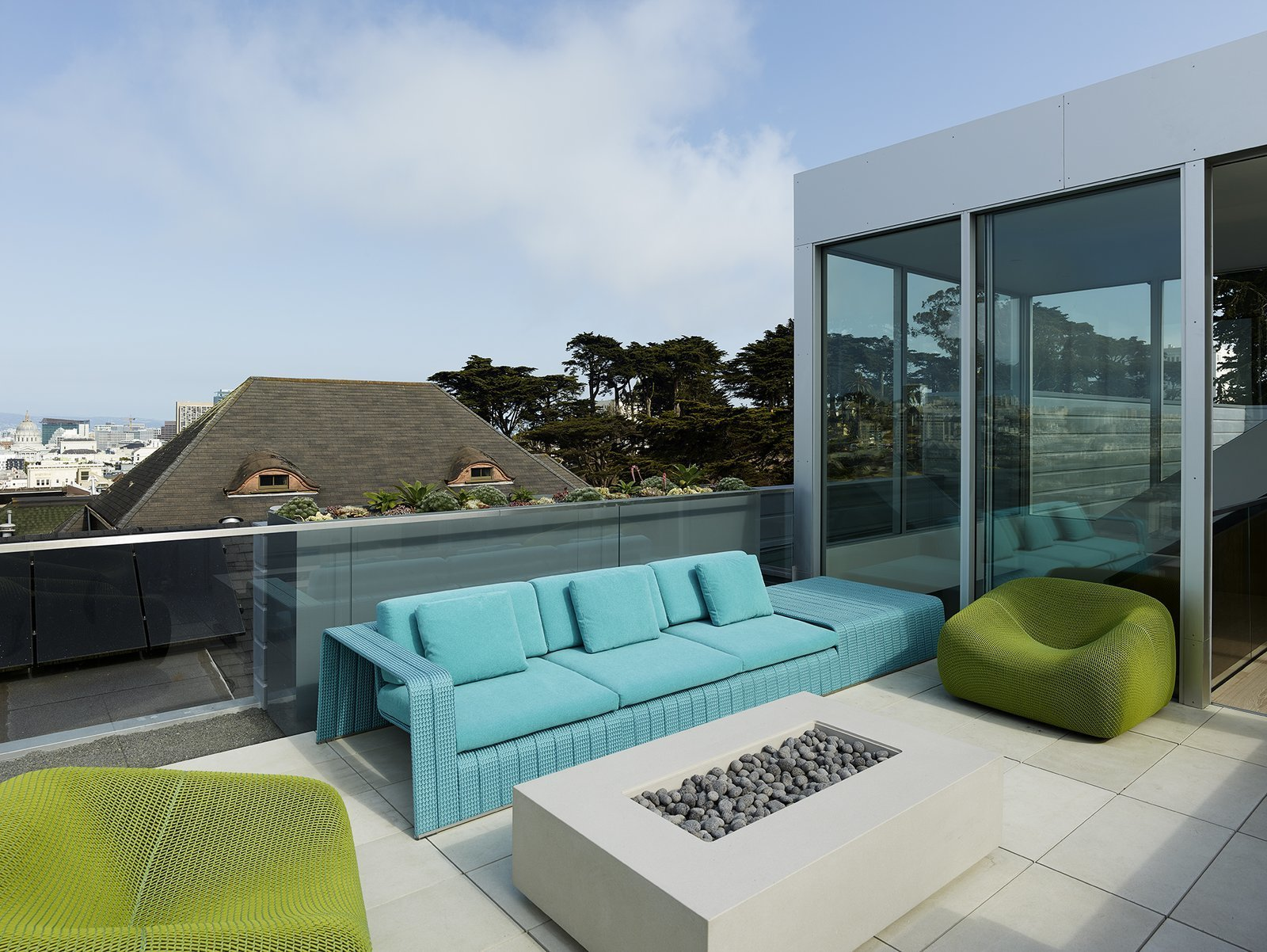 After: Alamo Square Residence roof top patio with short glass wall outdoor patio sofa and chairs with a rectangular outdoor firepit