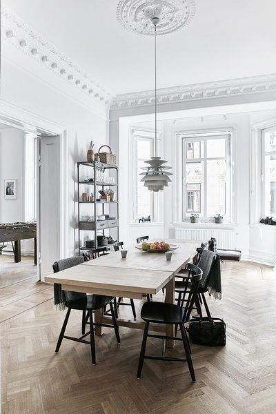 A Snowball pendant by Poul Henningsen for Louis Poulsen hangs in the dining room; the J46 chairs are by Poul M. Volther. - Gothenburg, Sweden Dwell Magazine : September / October 2017