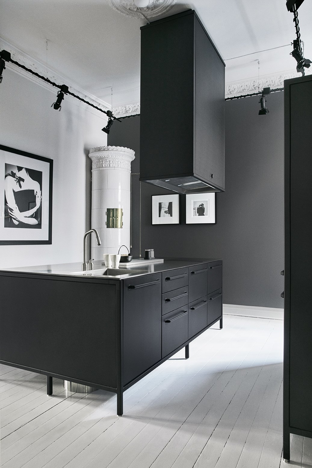 Kitchen, Metal Counter, Drop In Sink, Track Lighting, Cooktops, Range Hood, and Painted Wood Floor When creative director Martin Ringqvist and his wife, My, a teacher, moved back to Sweden after a year in Los Angeles, they wanted an authentic, warm space to live in with their two children. The kitchen's matte-black Vipp system is paired with an antique white ceramic tile stove that was typical in the late 19th century. Although it's not operable, the stove is used by the couple as a staging ground for illuminated candles and a storage space for an iPad that controls the home's sound system.  Photo 6 of 10 in Dwell's Top 10 Kitchens of 2017 from A Careful Renovation Brings a 19th-Century Flat in Gothenburg Back to Life