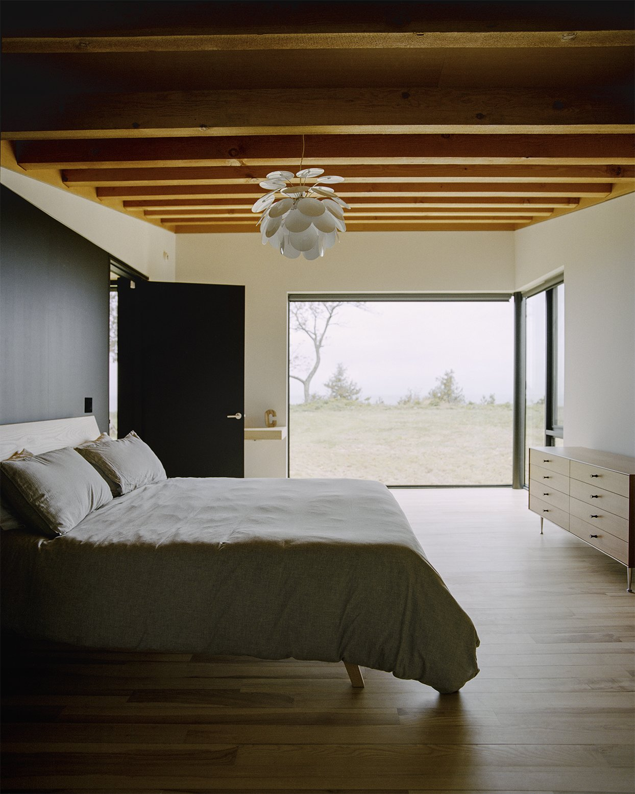 Bedroom, Dresser, Light Hardwood Floor, Shelves, Bed, and Pendant Lighting In the master bedroom, the ash bed was designed by Desai Chia  and fabricated by Gary Cheadle  of Woodbine; the dresser is by  George Nelson for Herman Miller. Panes by Western Windows  appear throughout the home. - Leelanau County, Michigan Dwell Magazine : September / October 2017  Best Photos from Plagued Ash Trees Were Repurposed to Create This Charred-Cedar Clad Home on Lake Michigan