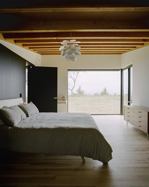 In the master bedroom, the ash bed was designed by Desai Chia  and fabricated by Gary Cheadle  of Woodbine; the dresser is by  George Nelson for Herman Miller. Panes by Western Windows  appear throughout the home. - Leelanau County, Michigan Dwell Magazine : September / October 2017