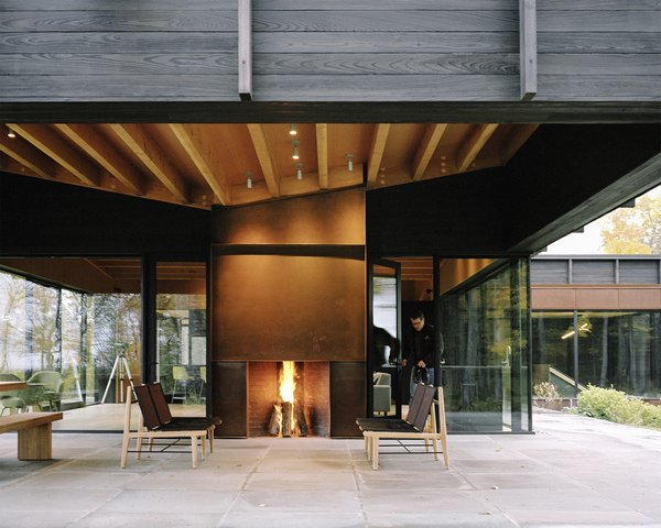 The home's undulating roof, composed of exposed wood beams and plywood sheathing, references the rolling terrain. A Cor-Ten steel–clad outdoor fireplace was built by BRD Construction; the same material was used for the interior fireplace, as surround on some windows, as cladding for the garage door, and on the chimney. The lounge chairs are from the Finn Collection from Design Within Reach. Tim Kirby of Surface Design Inc. tackled  the site's landscape architecture. - Leelanau County, Michigan Dwell Magazine : September / October 2017