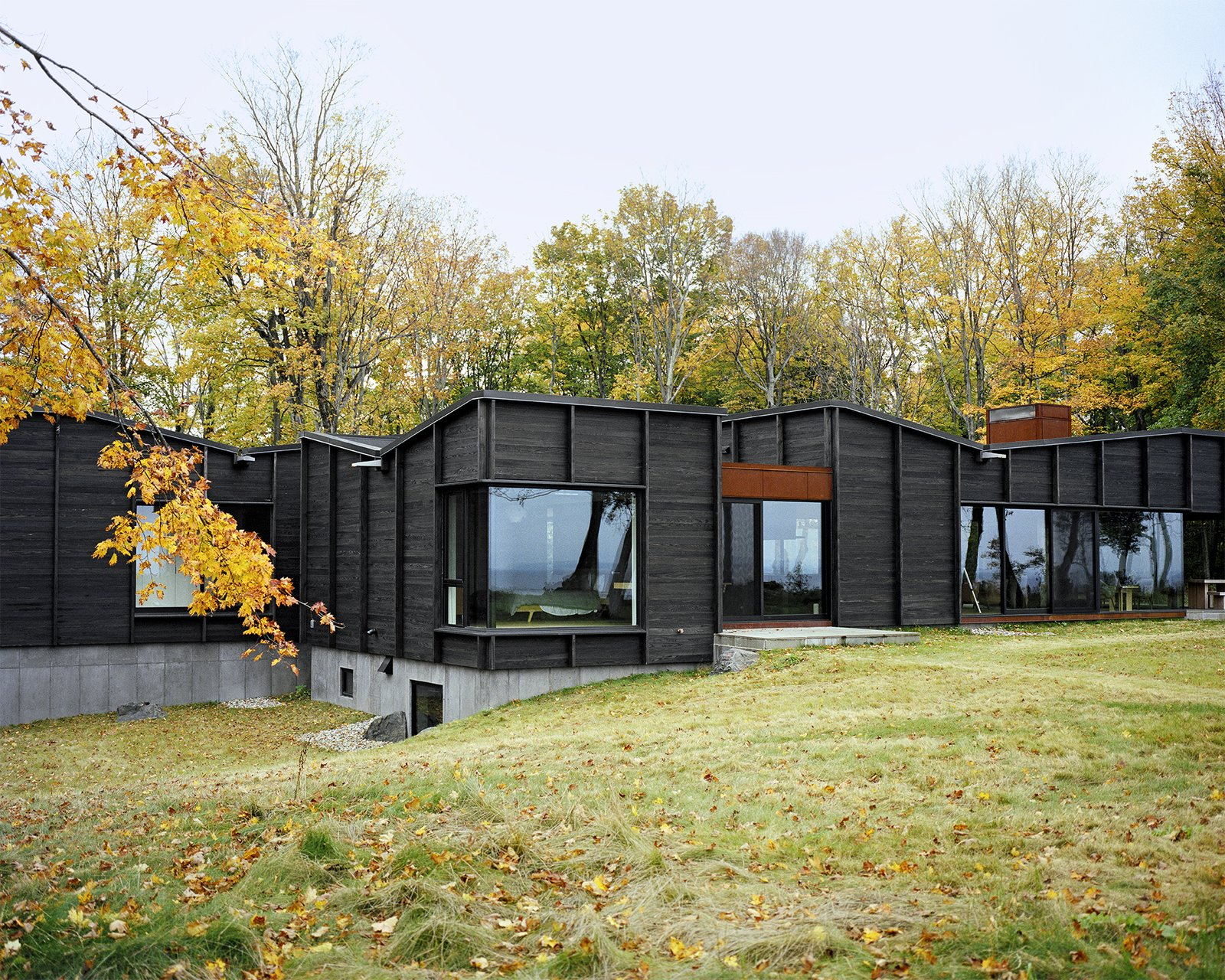 Exterior, House Building Type, and Wood Siding Material Three interconnected structures—one for communal spaces, one for the master suite, and one for the three children's bedrooms—are linked via a glass-enclosed breezeway that also serves as the entrance and dining area. - Leelanau County, Michigan Dwell Magazine : September / October 2017  Best Photos