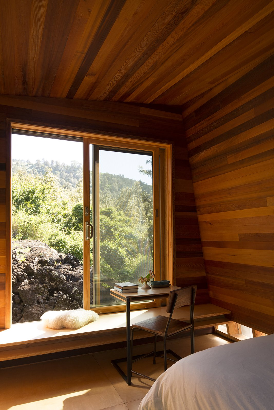 Windows, Sliding Window Type, and Wood Detailed in cedar paneling and plywood, Mauka was oriented to catch the sunrise. The table is by Moore's firm, FLOAT.  Maui, Hawaii Dwell Magazine : September / October 2017  Photo 4 of 9 in Two Tiny Pavilions Respectfully Perch Atop a Lava Flow on Maui