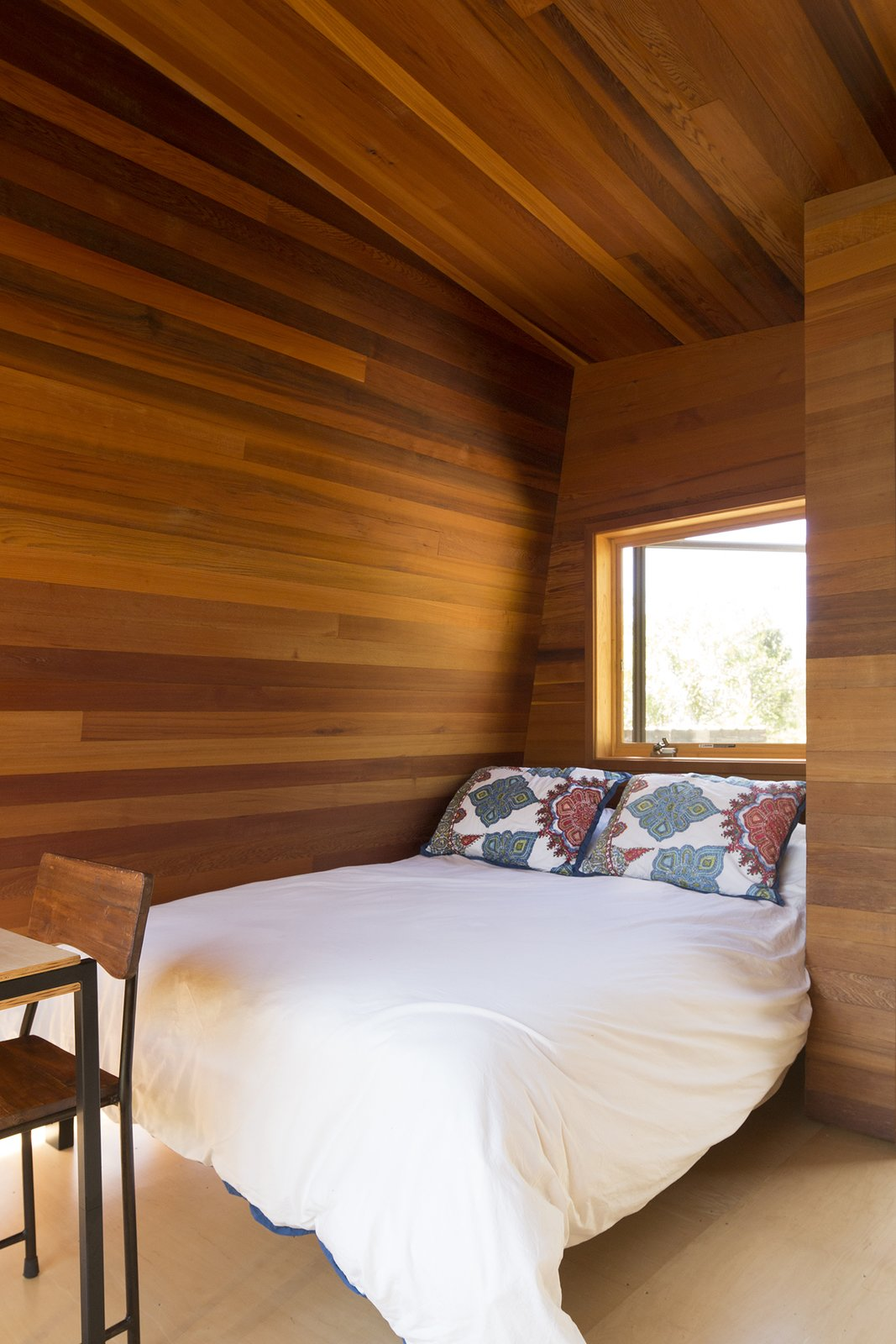 """Bedroom, Bed, and Chair """"The goal of the design was to amplify the site's natural phenomena, so that the luxury comes from the surroundings."""" Erin Moore, designer  Maui, Hawaii Dwell Magazine : September / October 2017  Best Photos from Two Tiny Pavilions Respectfully Perch Atop a Lava Flow on Maui"""