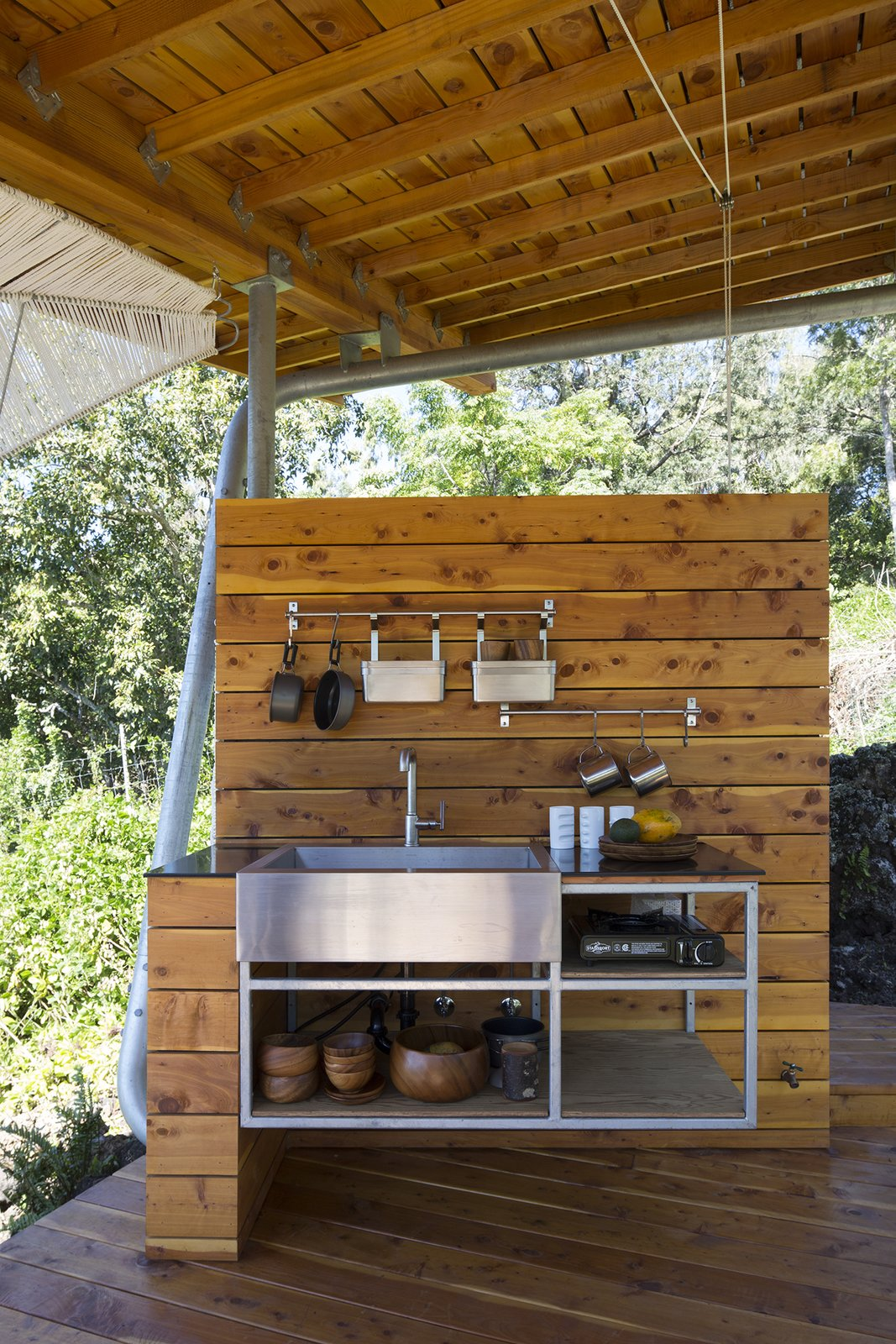 Outdoor and Small Patio, Porch, Deck The kitchen contains a Kohler sink and pot racks from IKEA.  Maui, Hawaii Dwell Magazine : September / October 2017  Photo 8 of 9 in Two Tiny Pavilions Respectfully Perch Atop a Lava Flow on Maui