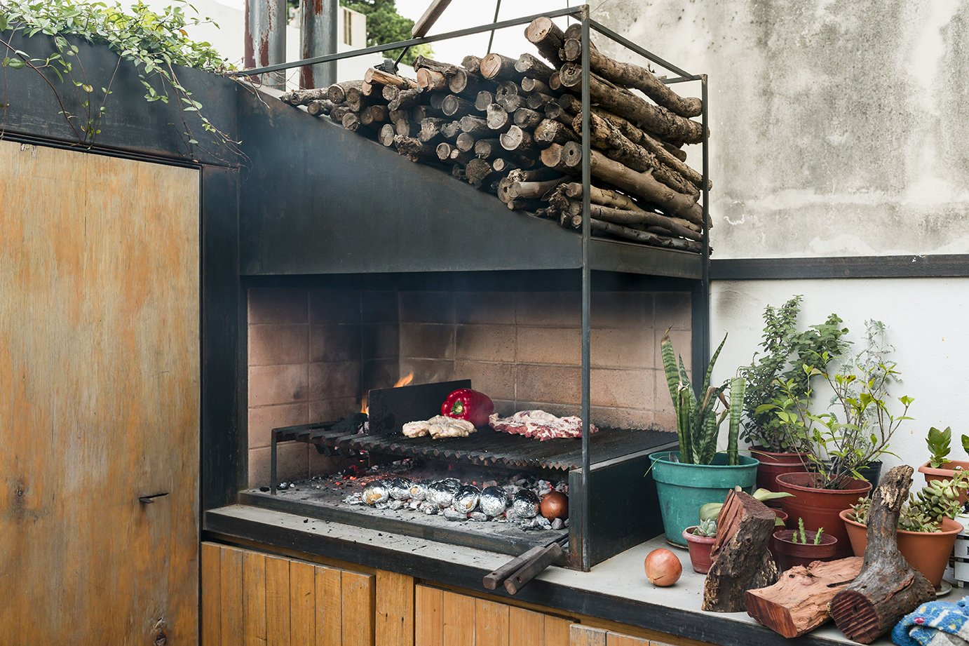 Outdoor and Small Patio, Porch, Deck A sleek version of the traditional  parrilla, or grill, handcrafted  by Oficios Asociados, has pride  of place on the patio counter. - Buenos Aires, Argentina Dwell Magazine : September / October 2017  Best Photos from An Architect Turns His Small, Dark Apartment in Buenos Aires Into a Bright and Airy Home
