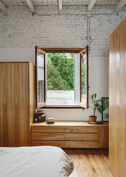 "Demolition exposed a high, wood-beamed ceiling, which added ""cubic meters of air"" to the apartment, says Hernán. The bedroom is furnished with custom pieces made of Paraiso wood. - Buenos Aires, Argentina Dwell Magazine : September / October 2017"