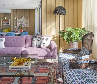 Eleni Katsarou's new Chicago apartment is an explosion of color. Graphic Fornasetti pillows rest on a pixelated-pink Carlton sectional by BoConcept next to cane back chairs upholstered in Quatrefoil fabric by Alexander Girard. - Chicago, Illinois Dwell Magazine : September / October 2017