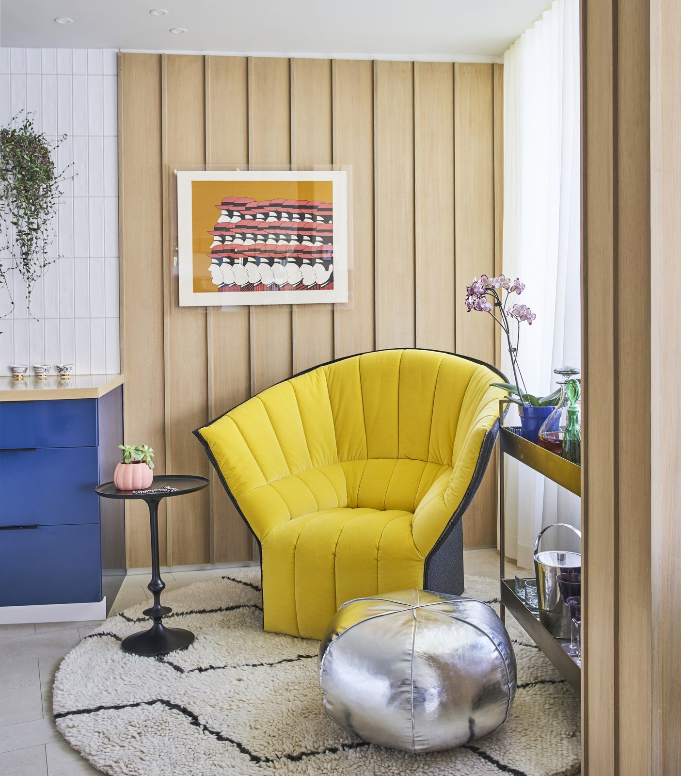 Living, Chair, End Tables, Rug, and Cork Near the kitchen, a Moel chair by Inga Sempé for Ligne Roset joins a bar trolley, side table, and pouf from Crate and Barrel. A Yannis Gaitis lithograph hangs on a wall of white oak plywood. Architect Mike Shively came up with the vertical strips to add texture. - Chicago, Illinois Dwell Magazine : September / October 2017  Best Living Cork Chair Photos from An Interior Designer Helps His Mother Turn Her 1960s Chicago Apartment Into a Colorful Haven