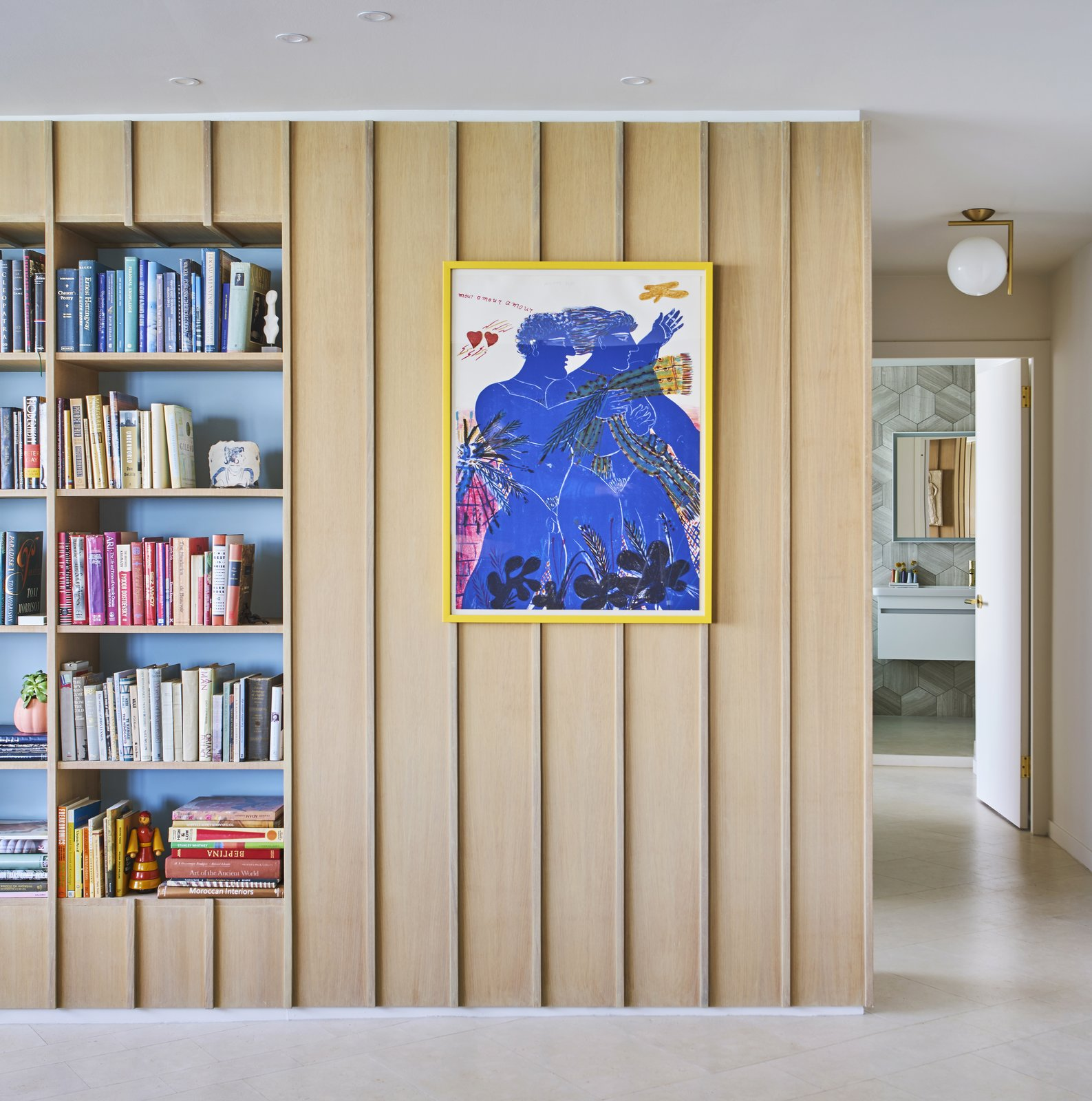 Cork Floor, Storage Room, and Shelves Storage Type An Alekos Fassianos lithograph and soft blue niches offset the wood paneling. An IC lamp by Michael Anastassiades hangs in the hallway. - Chicago, Illinois Dwell Magazine : September / October 2017  Photo 3 of 8 in 8 Bright and Airy Wood-Paneled Spaces from An Interior Designer Helps His Mother Turn Her 1960s Chicago Apartment Into a Colorful Haven