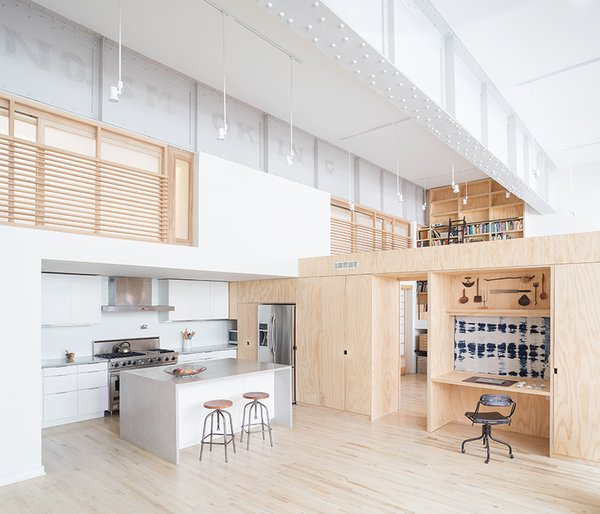 Architect Jeff Jordan designed plywood millwork to divide the 2,700-square-foot space. The nook is decorated with a shibori textile made by resident Bev O'Mara. The concrete kitchen island and countertops were fabricated by Brooklyn-based firm  Art in Construction.  Jersey City, New Jersey Dwell Magazine : September / October 2017