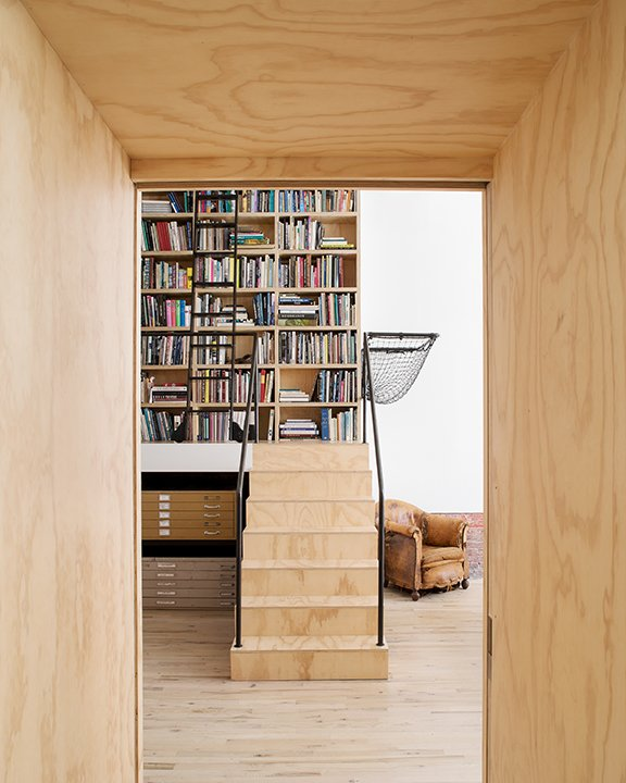 Staircase, Metal Railing, and Wood Tread A collection of art and design resources are stored on bookshelves.  Jersey City, New Jersey Dwell Magazine : September / October 2017  Best Photos from A 19th-Century Carriage House Is Transformed Into a Live/Work Residence For a Pair of Artists