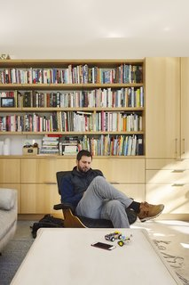 Tim reclines in an Eames Lounge. The bookcase behind him connects to the kitchen storage system.  Mill Valley, California Dwell Magazine : September / October 2017