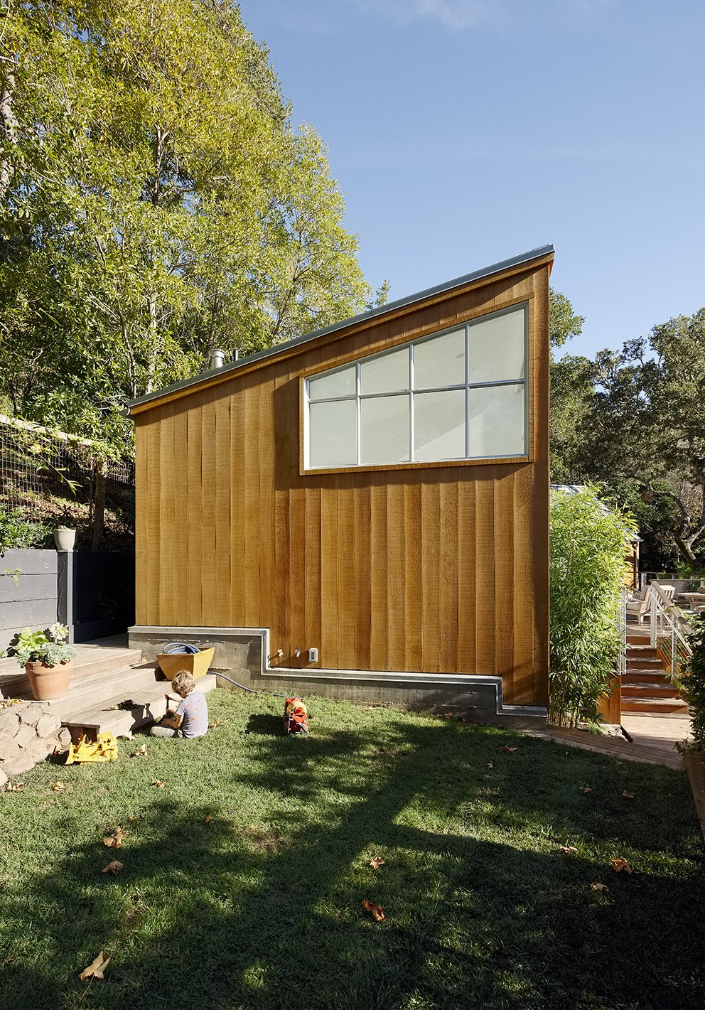 """Shed & Studio and Living Room The home's cedar siding is untreated, and its zinc  roof will """"mellow"""" over time, according to architect Peter Pfau.  Mill Valley, California Dwell Magazine : September / October 2017  Shed & Studio Living Room Photos from Space and Storage Needs Guide the Expansion of a Family's Cottage North of San Francisco"""