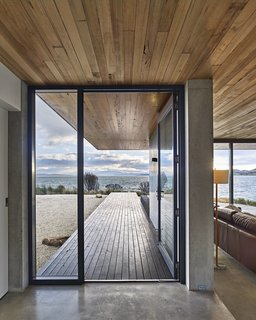 The dwelling's concrete slab meets a New Zealand pine deck at the custom steel entrance door.  Tasmania, Australia Dwell Magazine : September / October 2017