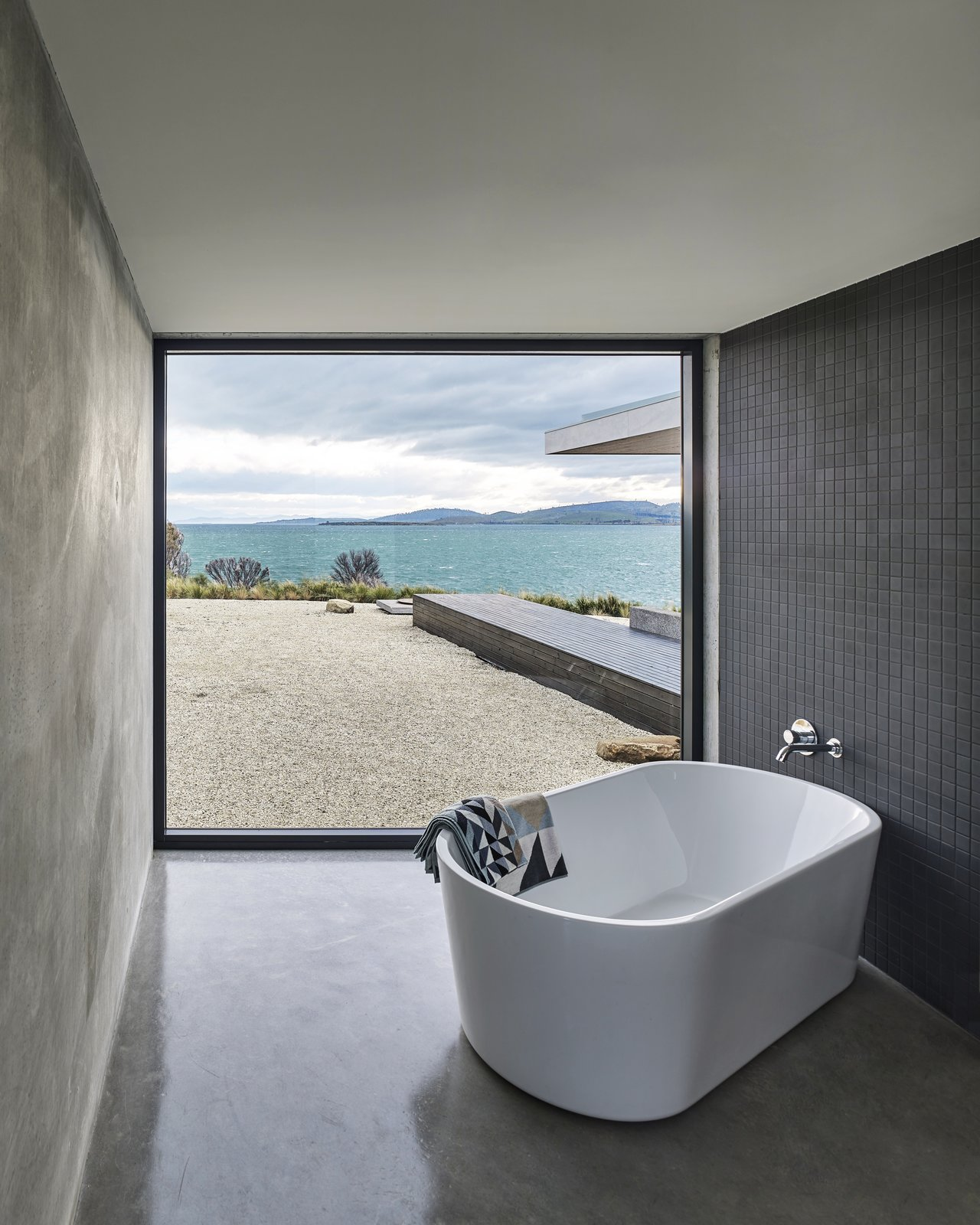 Bath Room, Concrete Floor, Freestanding Tub, and Soaking Tub The corner bathroom is defined by a freestanding Kado Lure 1760 tub and a powerful view of the bay.  Tasmania, Australia Dwell Magazine : September / October 2017  Photo 38 of 40 in 40 Modern Bathtubs That Soak In the View from A Semi-Modular Beach House in Tasmania Floats Over a Site That Survived a Bushfire