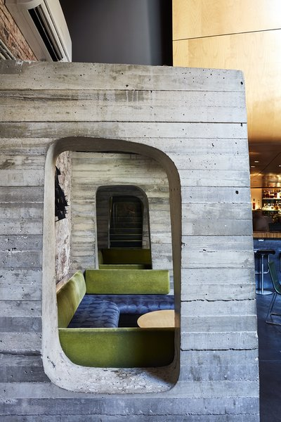 The first-floor auditorium/recording studio is located in a curvaceous wood pod that hovers above the bar in the basement. Concrete structural buttresses support the wall and act as stylized booth dividers. - New Haven, Connecticut Dwell Magazine : September / October 2017