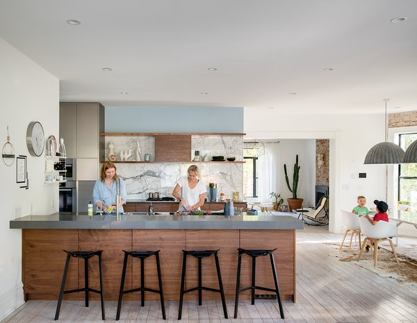 """The kitchen, dining area, and family room were originally three separate rooms,"" says Wilding.  ""We opened the space by knocking down walls and installing two large flush beams in the ceiling."" The original kitchen was located in what is now the family room. - Denver, Colorado Dwell Magazine : September / October 2017"