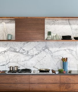 This Denver kitchen sets a marble backsplash, that continues up the wall as the backsplash for a display shelf, against walnut cabinetry and countertops of an alternate gray material.