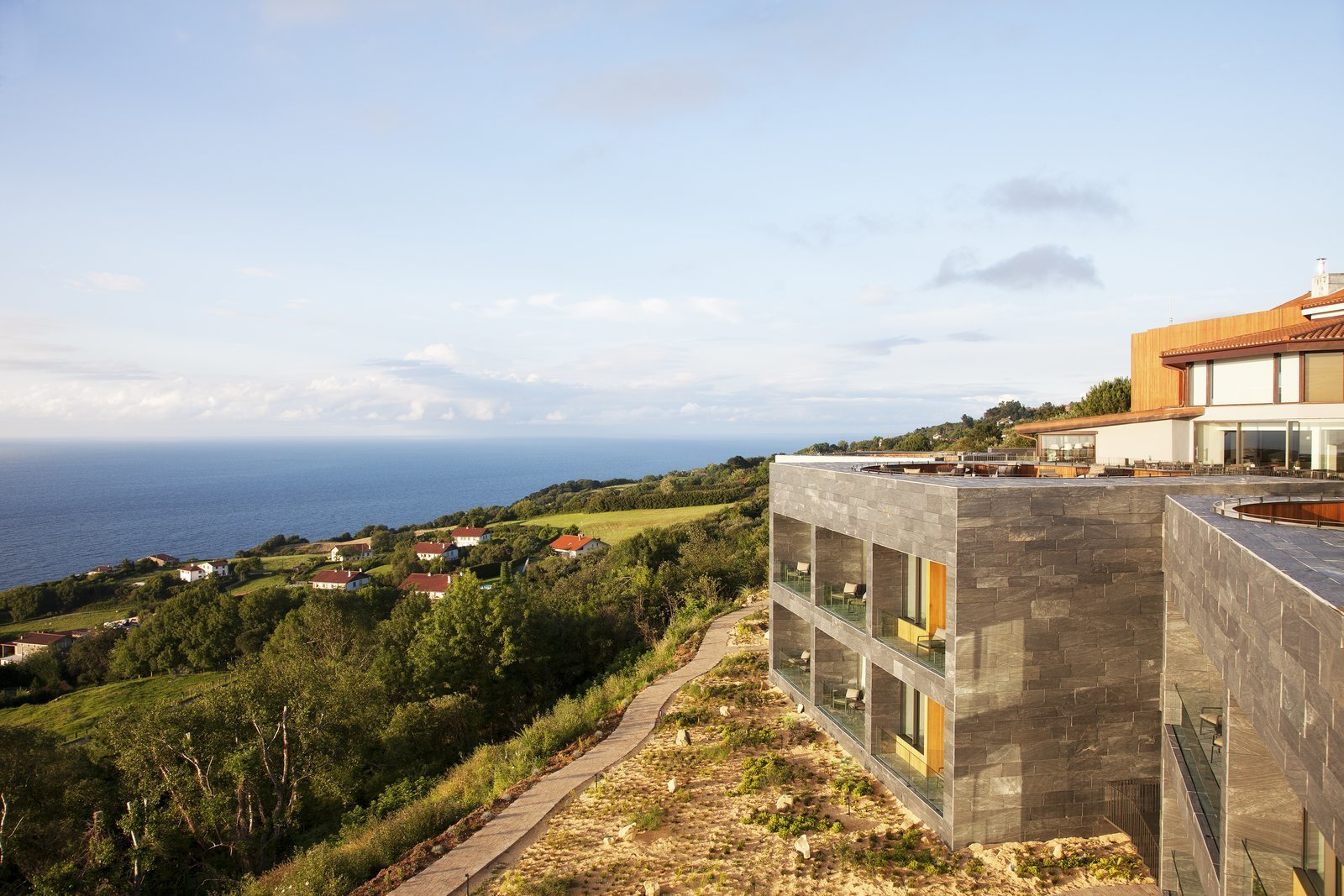 Exterior, Stone Siding Material, and Flat RoofLine Comprised of five stone cubicles that are built into the hillside facing the sea, the structure features a rooftop deck with slightly sunken outdoor pits for guests to enjoy. The terraces are connected by a series of planked decking and landscaped gardens that offer a spectacular panoramic view of the coastline.  Photo 1 of 13 in Spain's Basque Coast Gets a New Modern Hotel With a Michelin-Starred Restaurant