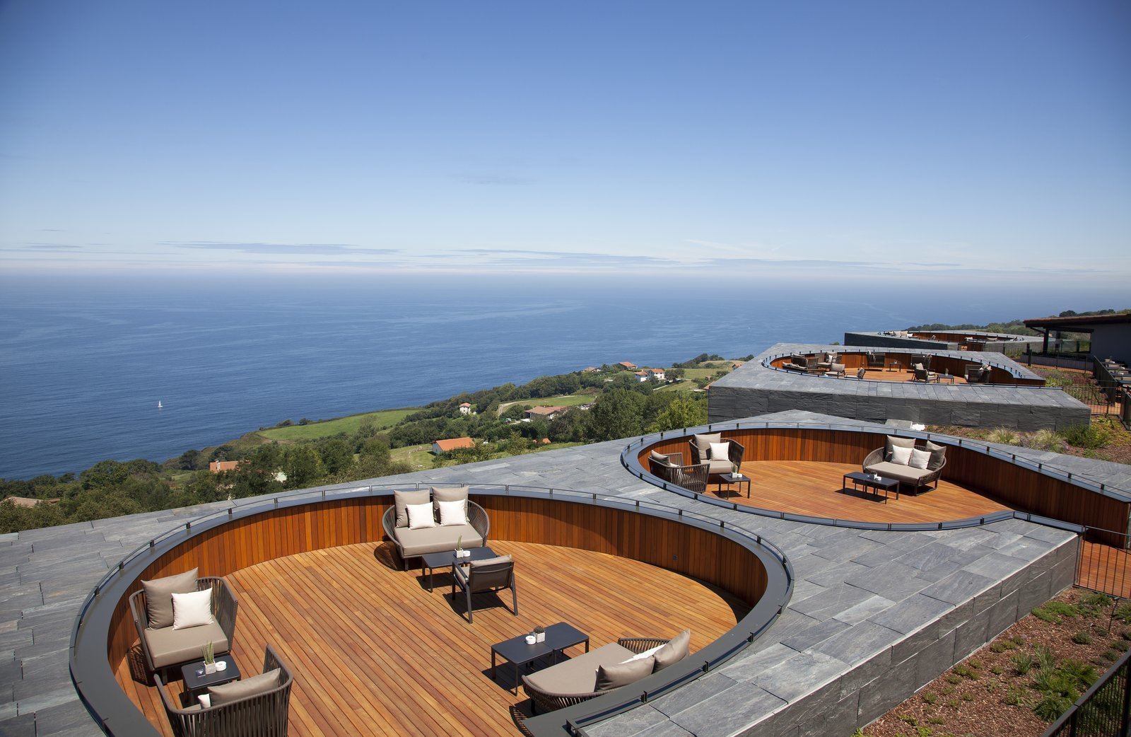 Outdoor, Decking Patio, Porch, Deck, Rooftop, and Wood Patio, Porch, Deck Six slightly sunken decks reminiscent of cozy conversation pits have form common outdoor space.  Photo 3 of 13 in Spain's Basque Coast Gets a New Modern Hotel With a Michelin-Starred Restaurant