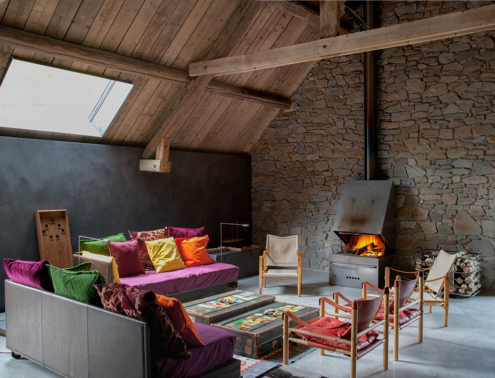 Living Room, Chair, Concrete Floor, Rug Floor, Standard Layout Fireplace, Wood Burning Fireplace, Sofa, Floor Lighting, and Coffee Tables The property has a soaring sense of space thanks to the vaulted ceilings.  Photo 5 of 16 in Stay at an Old Converted Train Station in the Belgian Countryside