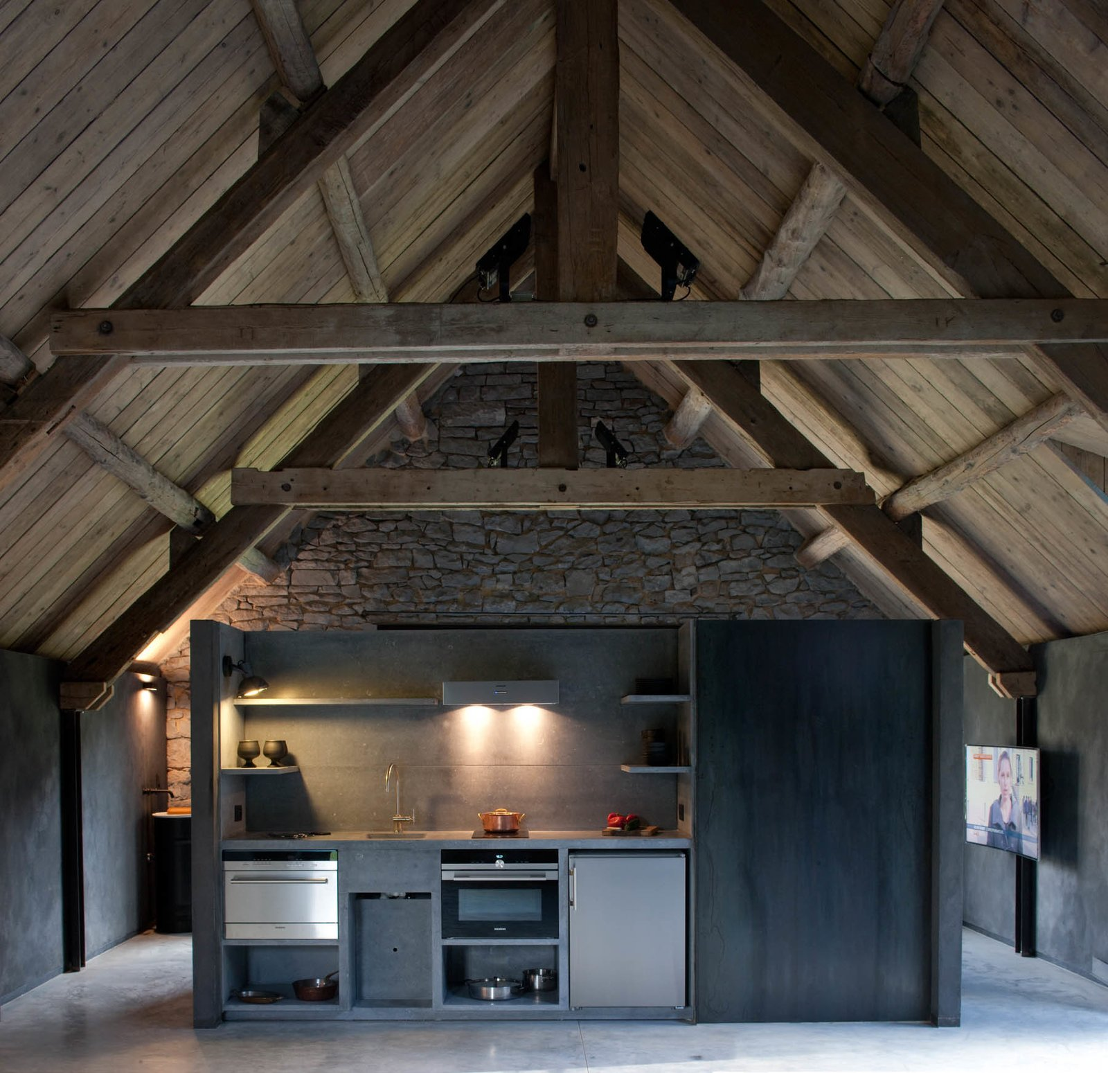 Kitchen, Concrete Floor, Wall Lighting, Wall Oven, Drop In Sink, Refrigerator, and Accent Lighting An additional kitchen has been placed in the loft for added convenience.  Photo 9 of 16 in Stay at an Old Converted Train Station in the Belgian Countryside