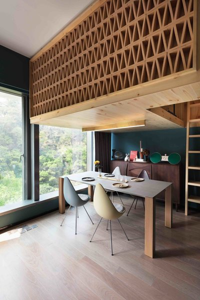 A tiny apartment in a Hong Kong high rise is named Mini Tree House Residence after its little lofted bedroom. Located in the residential neighborhood of Ho Man Tin in Kowloon, Hong Kong, this apartment was designed with a box-loft bedroom that's suspended above the main living and dining area. The little nook looks out to views of tree canopies along the hillside where the condominium is sited.