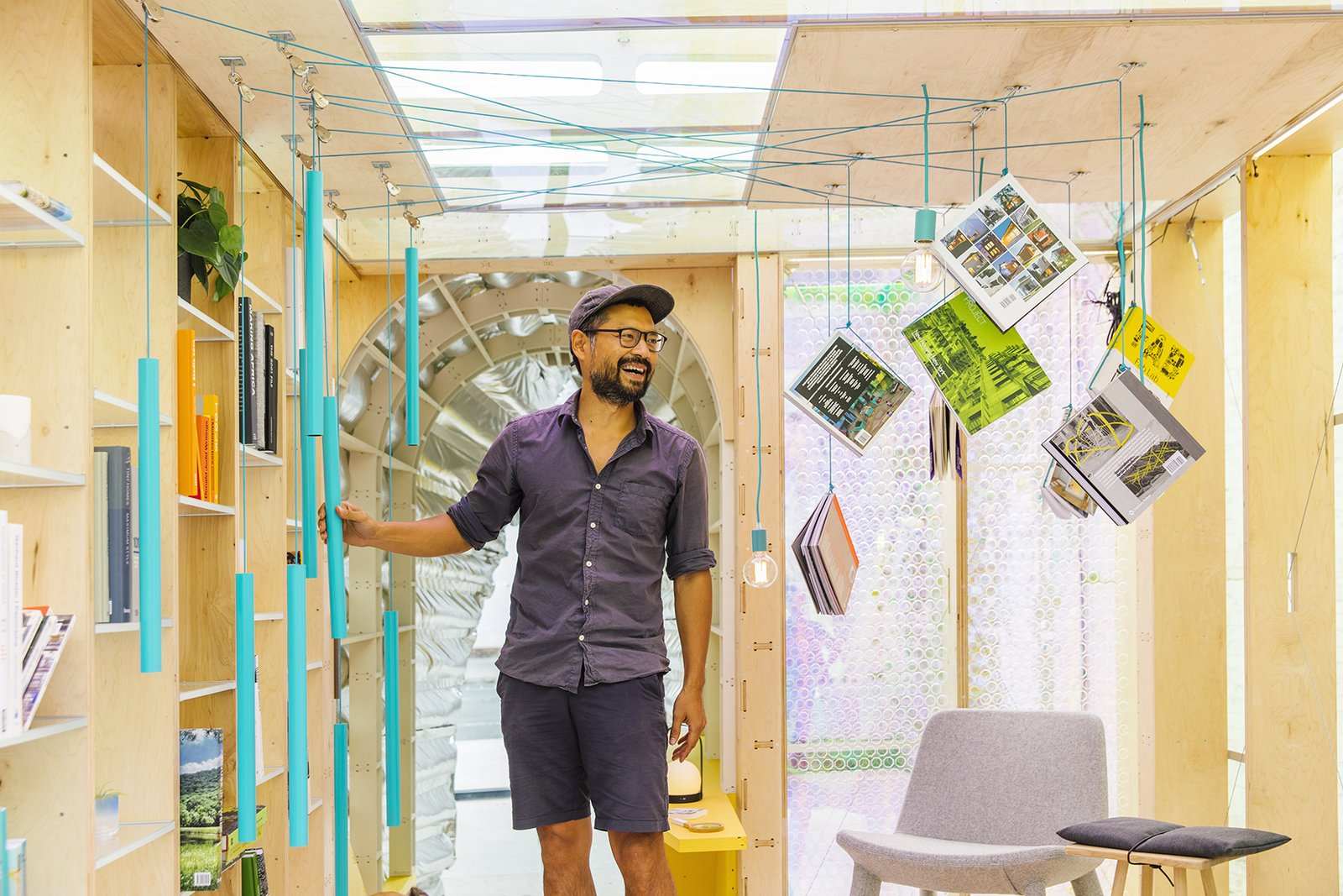 """The home's """"library"""" features books hanging from the ceiling via a stylish turquoise counterweight.  Photo 6 of 9 in A Vibrant Cabin in NYC Explores the Future of Urban Living"""