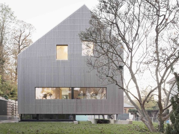 This prefabricated home in France was built to embrace the neighborhood.   Along a tree-lined street in the small community of Marly-le-Roi near Paris, most of the homes have high fences on both sides, which hide and isolate neighbors from each other. But the owners of this 1,561-square-foot, three-level CLT prefab home wanted a more open atmosphere, as well as a better visual and spatial connection with its surroundings.