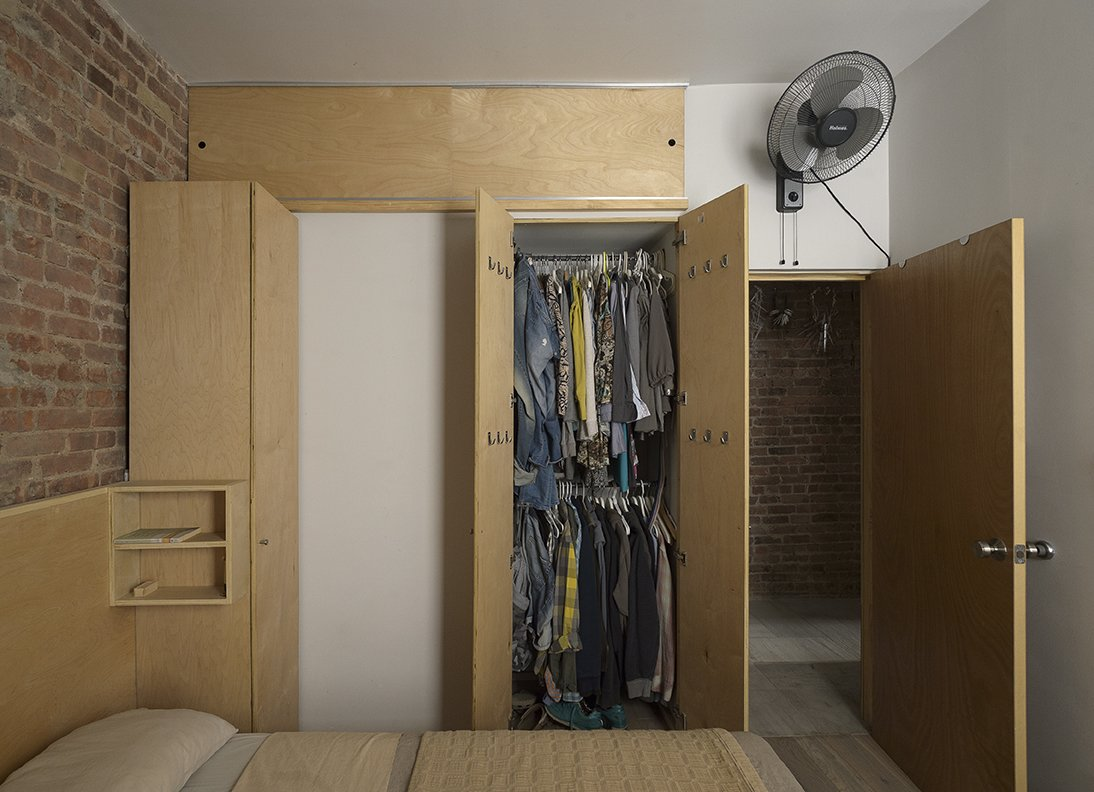 Bedroom, Wardrobe, Bookcase, Shelves, Light Hardwood, and Bed Three tall closets conceal the couple's belongings.  Best Bedroom Bed Wardrobe Bookcase Light Hardwood Shelves Photos from This Compact Apartment in NYC Is Full of Crafty Solutions