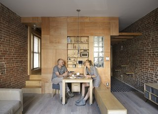 Peter and his wife, artist Olia Feshina, relax inside their apartment in New York's Washington Heights.  New York, New York Dwell Magazine : November / December 2017