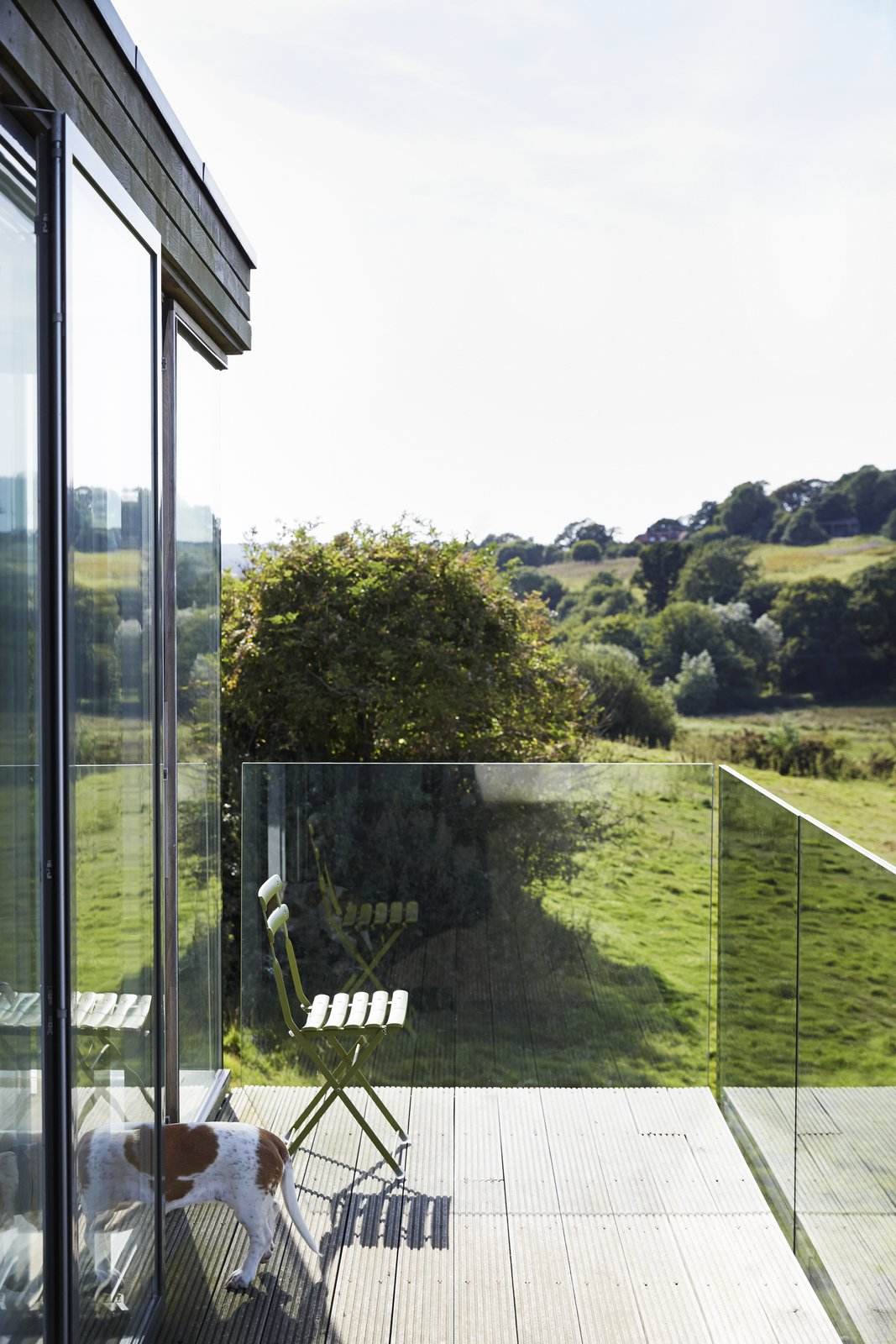 Outdoor and Wood Patio, Porch, Deck For uninterrupted views, the balcony is wrapped in glass panels.  Pett Level, England Dwell Magazine : November / December 2017  outside from Fall in Love With This British Architect's Colorful Weekend Retreat