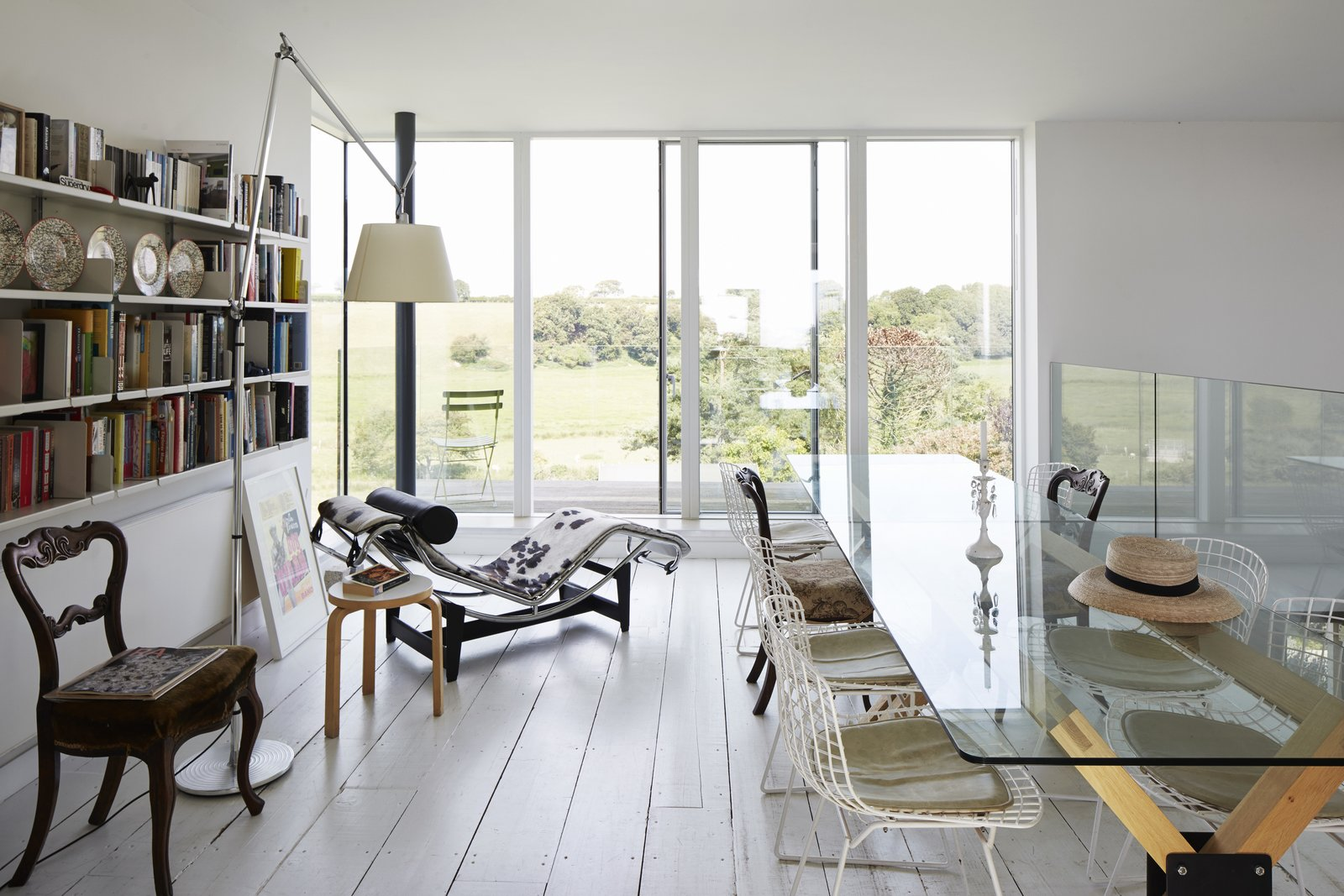 Dining, Chair, Table, Floor, Painted Wood, Shelves, and Lamps In the dining area, a custom table is paired with Bertoia chairs; an Alvar Aalto stool sits beside an LC4 chaise longue by Le Corbusier.  Pett Level, England Dwell Magazine : November / December 2017  Best Dining Lamps Table Chair Floor Photos from Fall in Love With This British Architect's Colorful Weekend Retreat