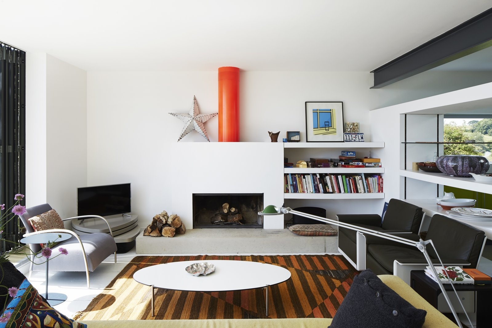 Living Room, Wood Burning Fireplace, Standard Layout Fireplace, Rug Floor, Floor Lighting, Chair, Painted Wood Floor, Sofa, Coffee Tables, End Tables, Shelves, and Storage A home near Rye, England, opens onto a deck through a Sunflex door. The living room features a sofa by Terence Woodgate, 620 chairs by Dieter Rams for Vitsœ, and an Oluce Atollo 239 lamp by Vico Magistretti. The wood-burning fireplace sits along one wall in the room, with a bright orange flue acting as a sculptural focal point.  Photo 11 of 14 in Fall in Love With This British Architect's Colorful Weekend Retreat