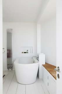 Nick got his wish of being able to watch the surf from the bathtub with the insertion of a sliver window in the master bath.  Pett Level, England Dwell Magazine : November / December 2017