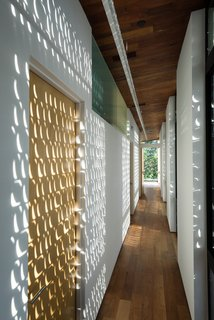 Light passing through the perforated shutters animates the upstairs. - Austin, Texas Dwell Magazine : November / December 2017