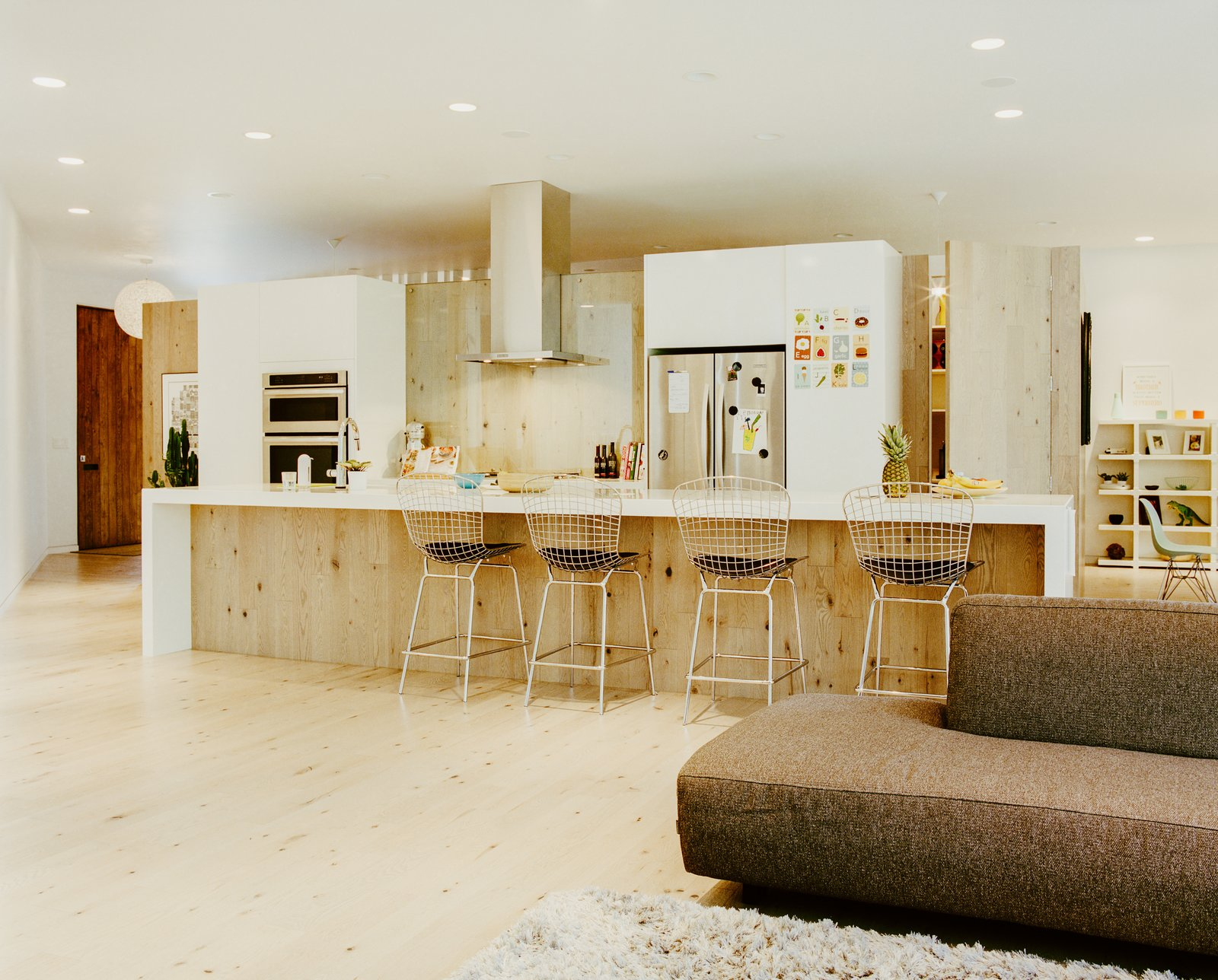Kitchen, Refrigerator, Wall Oven, Range Hood, White, Wood, Light Hardwood, Ceiling, and Recessed In the kitchen, Structube stools pull up to a Quartzforms countertop.  East St. Paul, Manitoba Dwell Magazine : November / December 2017  Best Kitchen Wood White Refrigerator Light Hardwood Ceiling Photos from The Parallelogram House Helps Reshape a Sleepy Canadian City