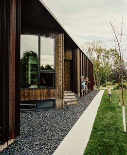 Beyond a bed of black granite rocks, an entrance is concealed in an alcove in the home's cedar-and-weathered-steel facade. The windows were manufactured by Duxton Windows & Doors.  East St. Paul, Manitoba Dwell Magazine : November / December 2017
