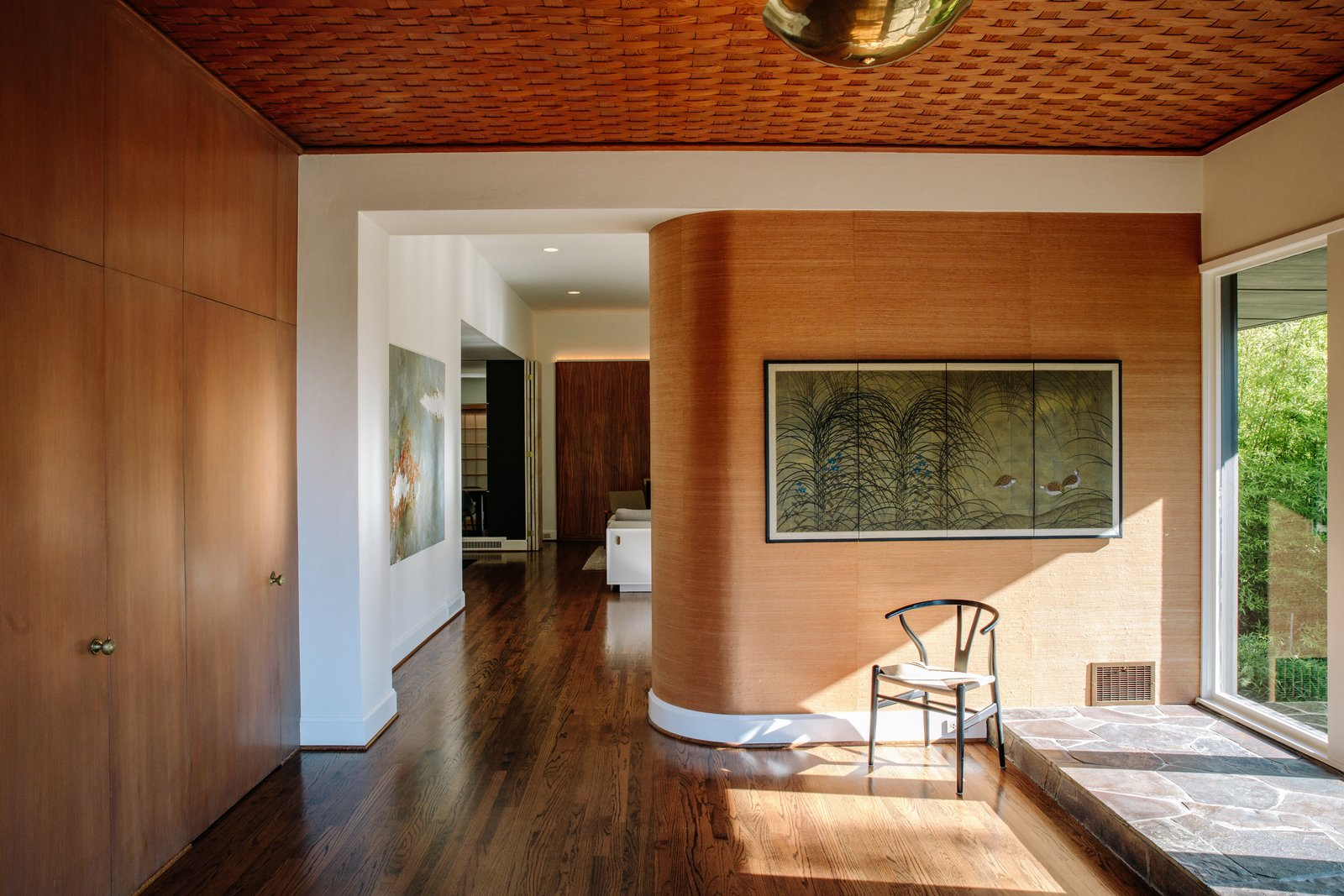 Living Room, Chair, Medium Hardwood Floor, and Ceiling Lighting A curved zebrawood wall greets visitors in the foyer.  Photo 3 of 15 in Nearly 80 Years Later, an Architect Rescues a Japanese-Inspired  Masterwork Designed by His Father