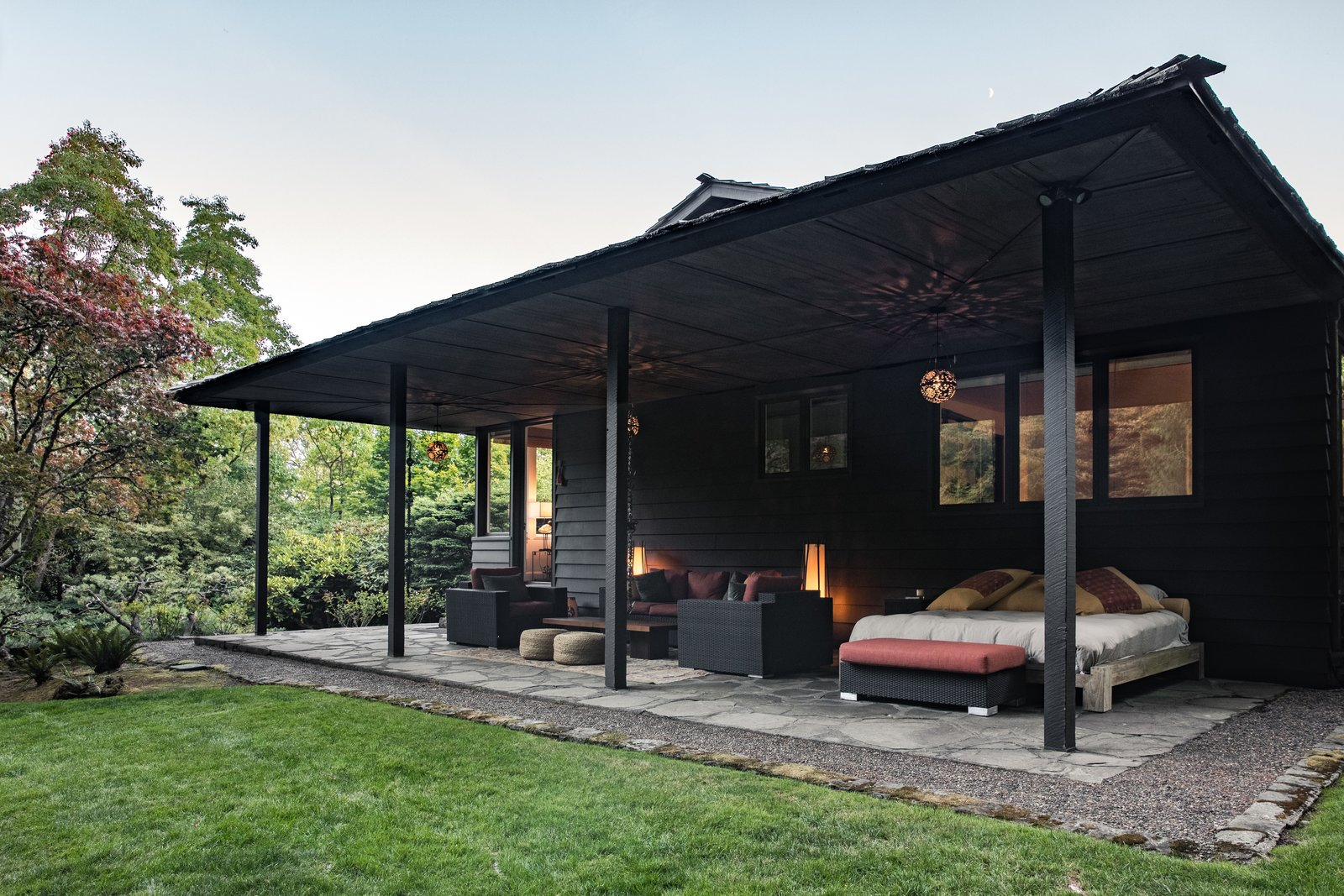 Outdoor, Pavers Patio, Porch, Deck, Grass, Trees, and Hardscapes The portico is used as a living room in Spring and Summer.  Photo 12 of 15 in Nearly 80 Years Later, An Architect Rescues a Japanese-Inspired  Masterwork Designed by His Father