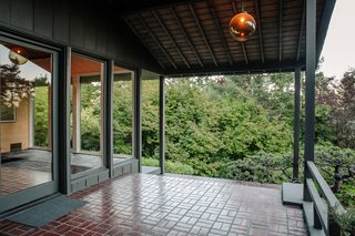 The front porch, clad with floor-to-ceiling glass windows, illuminates the foyer inside.