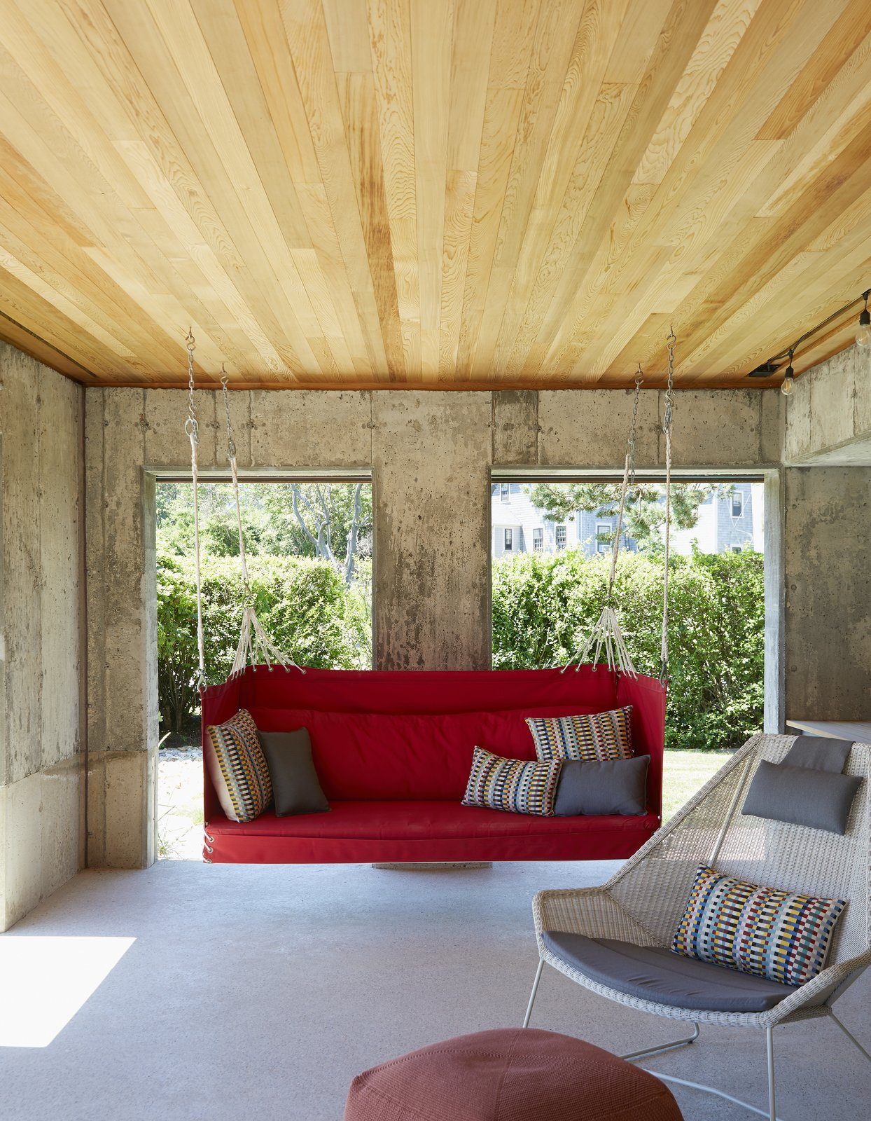 Living Room, Concrete Floor, Chair, and Ottomans A Penobscot Bay swing hangs beside the dining table in the porch. - Rockport, Massachusetts Dwell Magazine : November / December 2017  Best Photos from On the Coast of Massachusetts, a Prefab Ranch Is Totally Overhauled for a Wheelchair-User